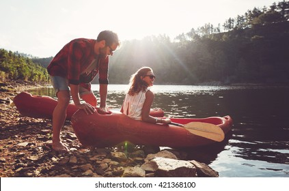 Young man pushes a canoe in the water while a woman sitting on the canoe. Couple going for kayaking in lake on a summer day.