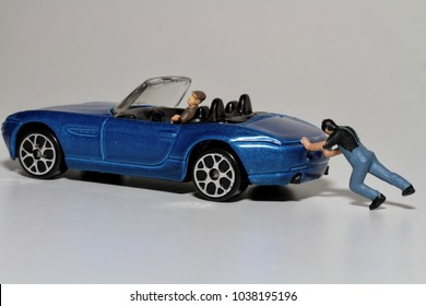 young man pushing a broken car in miniature