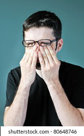 A young man pushing his glasses up and rubbing his eyes.
