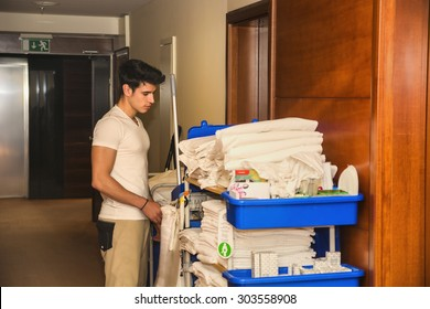 Young man pushing a housekeeping cart laden with clean towels, laundry and cleaning equipment in a hotel as he services the rooms