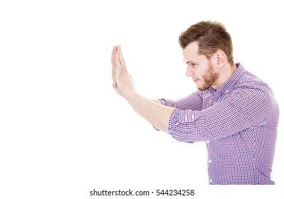 Young man pushing something isolated on a white background