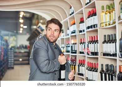 Young man puts a bottle of wine in his jacket during shoplifting