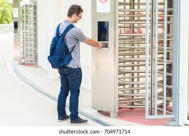 Young man puts the card into the reader system on security door