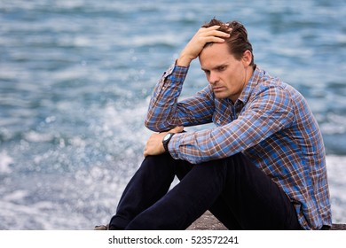 Young man puts hand on head and looks very distressed and worn out and is suffering from depression he is sitting by the ocean. Focus is soft.