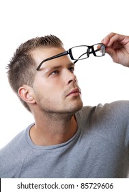 Young man puts his glasses on
