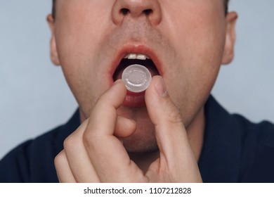 young man puts in his mouth a sucking pill for sore throat. Self-medication for flu and cold. Sick with a sore throat, mint for fresh breath. close up