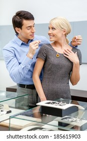 Young man puts necklace on his girlfriend at jeweler's shop. Concept of wealth and luxurious life
