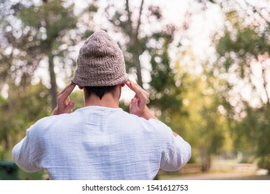 Young man puts on a hat to protect his head from the cold, he is on his back.