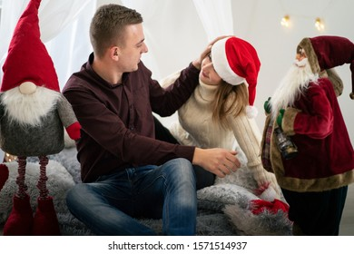 A young man puts a Santa Claus hat on the head of his beloved girlfriend. Woman laughs with her husband. Loving couple having fun in the new year in a bright room. Merry Christmas and Happy New Year
