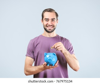 Young man putting coin in piggy bank on light background