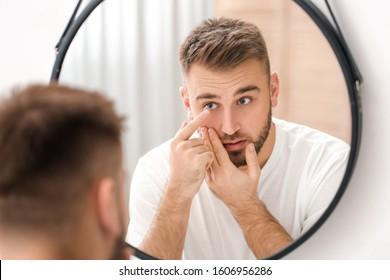 Young man putting in contact lenses near mirror