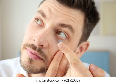 Young man putting contact lenses at home, closeup