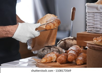 Young man putting croissant in paper bag with tongs in bakery