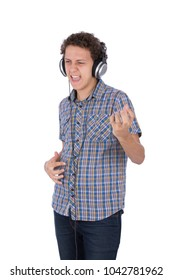 A young man putting the headphone and listening to music happy, dancing like he is playing guitar, isolated on a white background.