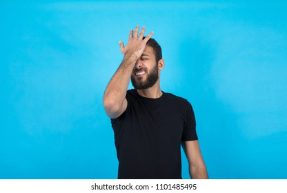 Young man putting his hand on the forehead remembering something important he forgets on a blue background.