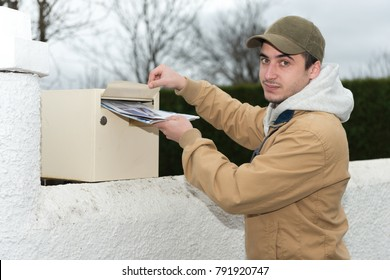 young man putting newspaper from the mailbox