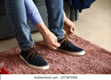 Young man putting on shoes in room