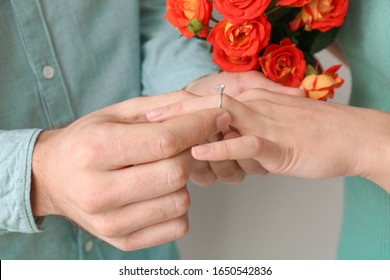 Young man putting ring on finger of his fiancee after marriage proposal, closeup