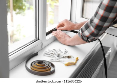 Young man putting sealing foam tape on window indoors