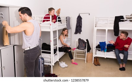 Young man putting things in personal locker in hostel dormitory