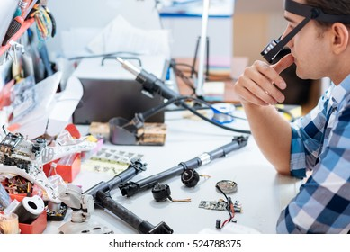 Young man putting together the drone in workroom