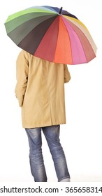 Young man in raincoat back portrait with colorful umbrella.