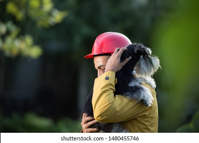 Young man in raincoat and with helmet holding dog in arms. Animal rescue team