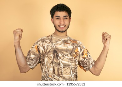 Young Man raise fist up on beige background