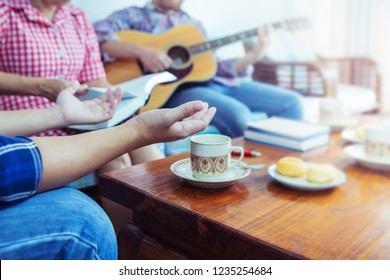 A young man raise hands up worship God while another person holding bible and plays guitar at home, Christian family, small group or house church worship concept