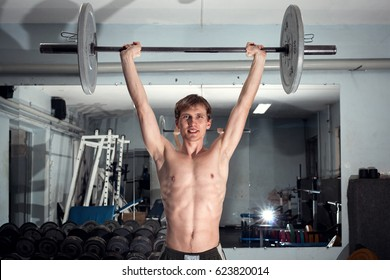 Young man raised the barbell in the old gym. Slender and thin, smiling