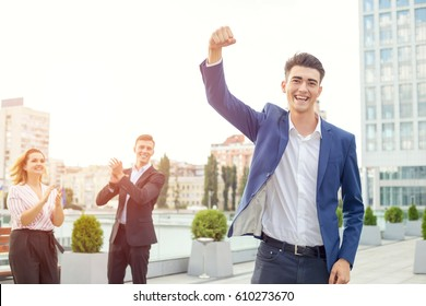 Young man raised his arms up as a sign of victory and success in business. Man against the backdrop of a group of its employees. Concept - business champion. Teamwork. Office workers - winning team.