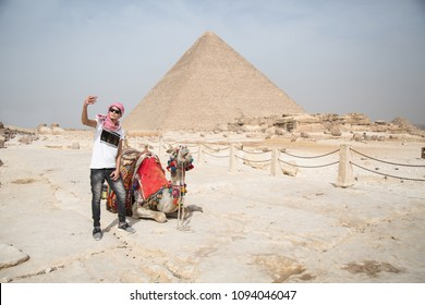 Young man raising his phone taking a selfie with the camel, the pyramid behind him in the background.