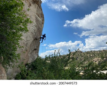 A young man is rappelling down a rock in the mountains.