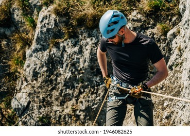 Young man rappelling down a rocky cliff, he is attached on rope with a figure eight and carabiner. Extreme adventure in the mountains.