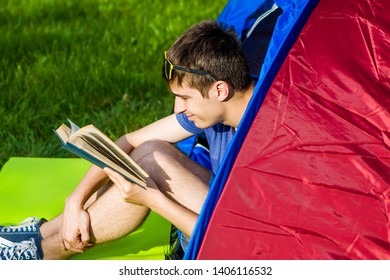 Young Man read a Book in the Tent on the Nature