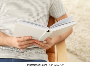 Young man reading book at home, closeup