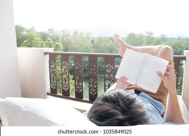 Young man reading a book lying on soft mattress in relaxing bed at terrace with green nature view. Fresh air in the morning of weekend or free day. Relax or education background idea.