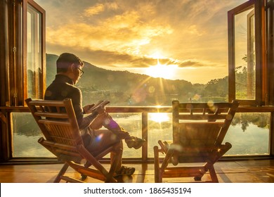 young man reading book near window and watching lake view at coffee shop in the morning sunrise, Ban Rak Thai village, Mae Hong Son province, Thailand. Travel concept