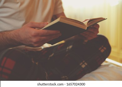 Young man reading book on bed at home, closeup