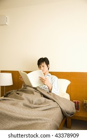 Young man reading a book on the bed