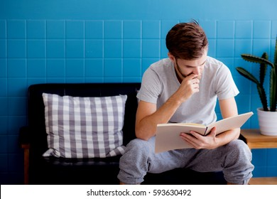 Young man reading book on sofa in the living room, education concept