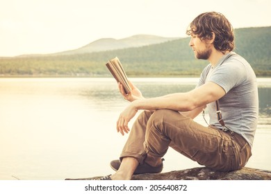 Young Man reading book outdoor with lake on background Summer vacations and Lifestyle concept