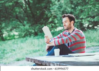 Jovem lendo um livro no parque