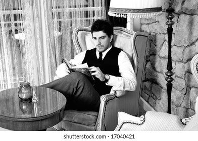 young man reading book and relaxing in luxury indoor