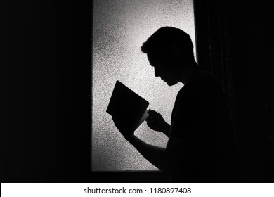 Young man reading book silhouette. Learning and religion concept.