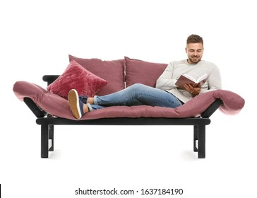 Young man reading book while relaxing on sofa against white background
