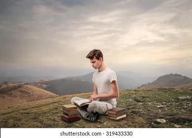 Young man reading books while sitting in the mountains
