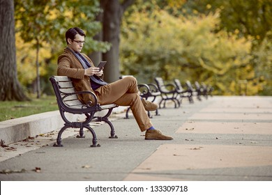 Young Man Reading With A Digital Tablet At The Park