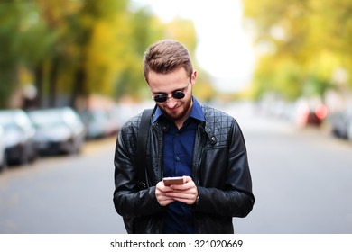Young man reading funny text message in autumn park