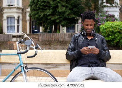 young man reading his text messages sat on a bench